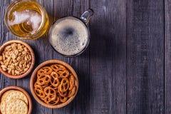 Bière avec des bretzels, des biscuits et des écrous photos stock