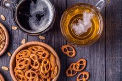 Bière avec des bretzels, des biscuits et des écrous images libres de droits