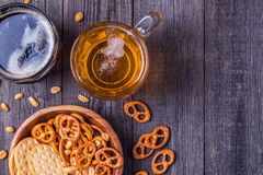 Bière avec des bretzels, des biscuits et des écrous image libre de droits