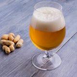 Bière avec la mousse et les arachides Photos stock