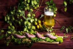 Bière avec les crevettes et la salade sur une table en bois Image stock