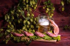 Bière avec les crevettes et la salade sur une table en bois Photos stock