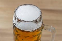 Bière avec une tête écumeuse dans une tasse de bière en verre Image stock