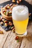 Bière blonde écumeuse et fèves salées frites en gros plan Vertica photographie stock libre de droits