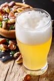 Bière blonde avec la mousse et les fèves salées frites en gros plan Vert photos stock