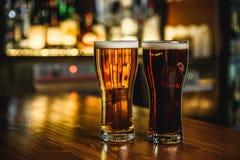 Bière blonde et foncée sur un fond de bar Image libre de droits