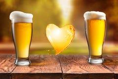 Bière d'amour Bière en verre avec l'éclaboussure de coeur sur la table en bois encore Image stock