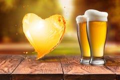 Bière d'amour Bière en verre avec l'éclaboussure de coeur sur la table en bois encore Photos stock