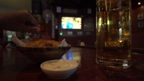 Bière d'homme et casse-croûte potables de consommation dans la barre de sport avec le fond du match de football TV banque de vidéos