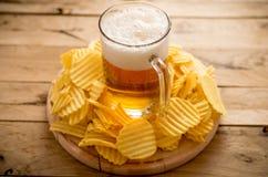 Bière dans la tasse, frites, fond en bois, nourriture de confort Photos stock