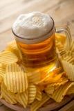 Bière dans la tasse, frites, fond en bois, nourriture de confort Image stock