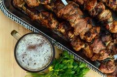Bière dans un verre, viande grillée sur des brochettes, herbes fraîches images libres de droits