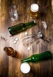 Bière de chaos sur la table en bois Bouteilles et verres de bière Images stock