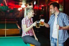 Bière de couples heureux et billard potables de jouer Images libres de droits