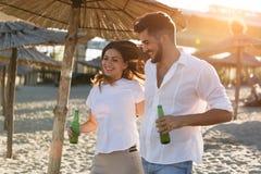 Bière de sourire et potable de couples heureux à la plage Images libres de droits