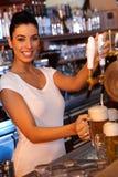 Bière de tapement de barman attirant dans le bar photographie stock
