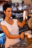 Bière de tapement de barman féminin dans la barre image stock