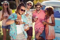 Bière de versement d'homme heureux dans un verre tandis que ses amis se tenant à l'arrière-plan Photographie stock