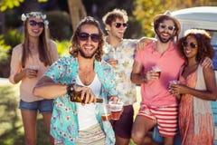 Bière de versement d'homme heureux dans un verre tandis que ses amis se tenant à l'arrière-plan Images stock