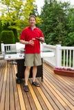 Bière de versement d'homme mûr dans le verre tandis que dehors sur le patio ouvert Photo libre de droits