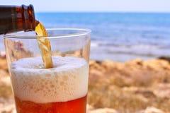 Bière de versement dans la plage photographie stock libre de droits