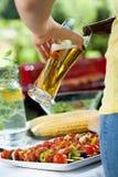 Bière de versement de femme sur le barbecue Photographie stock