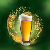 Bière en verre avec l'éclaboussure sur le fond vert image stock