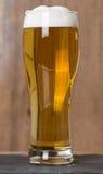 Bière en verre sur le fond en bois Photographie stock