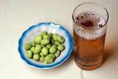 Bière et arachides avec un goût de wasabi Photo stock
