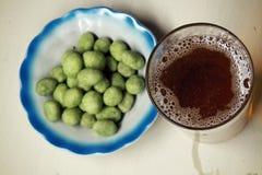 Bière et arachides avec un goût de wasabi Photographie stock libre de droits