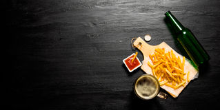 Bière et fritures avec la sauce tomate sur le tableau L'espace libre pour le texte Image libre de droits
