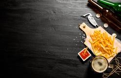 Bière et fritures avec la sauce tomate sur le tableau L'espace libre pour le texte Photos libres de droits