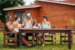 Bière et soude potables de sourire de personnes à la table dehors Image libre de droits