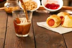 Bière foncée de versement dans le verre avec des porcs dans une couverture, ketchup, NU image stock