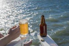 Bière fraîchement versée dans la tasse sur la plate-forme de bord de la mer avec la bouteille Image libre de droits