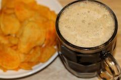 Bière noire mousseuse et pommes chips croustillantes du plat blanc photo stock
