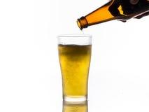 Bière pleuvant à torrents dans la tasse Images stock