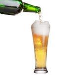 Bière pleuvant à torrents de la bouteille dans la glace d'isolement Photo stock