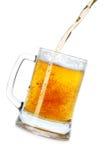 Bière pleuvante à torrents dans la tasse Image libre de droits