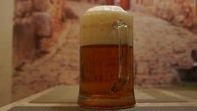 Bière pleuvante à torrents Bière de lumière froide Bière de métier Une pinte de bière blonde banque de vidéos