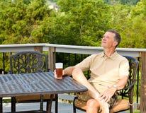 Bière potable d'homme aîné dans le jardin Photographie stock