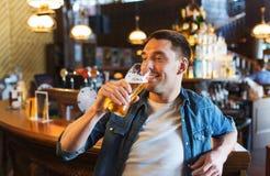 Bière potable d'homme heureux à la barre ou au bar Image libre de droits