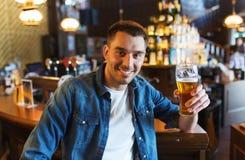 Bière potable d'homme heureux à la barre ou au bar photos libres de droits