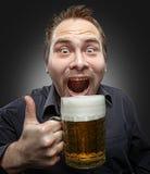 Bière potable d'homme heureux de la tasse Image stock