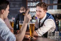 Bière potable d'homme sûr à la barre L'homme tient le verre de bière Photographie stock