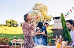 Bière potable de femme dans un barbecue avec des amis Photographie stock libre de droits