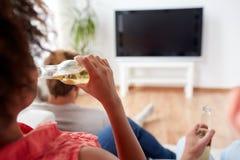 Bière potable de femme et TV de observation à la maison Image stock