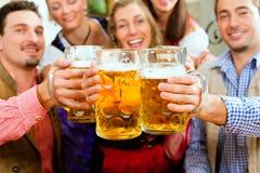 Bière potable de gens dans le pub bavarois photos libres de droits