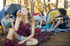 Bière potable de jeune femme tout en se reposant au terrain de camping Images stock