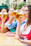 Bière potable de personnes dans le restaurant ou le bar bavarois Image libre de droits